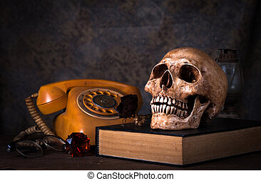 Group of objects on wood table. old book, human skull ,old rusty kerosene lamp,old telephone, Still life
