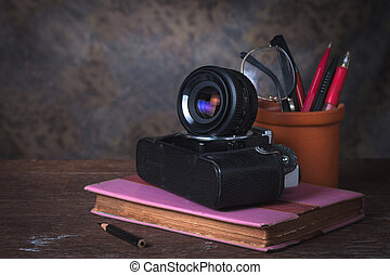 Group of objects on wood table. old book, old camera, glasses an