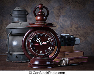 Group of objects on wood table. old clock, old rusty kerosene lamp ,old books , pencil, old camera, Still life