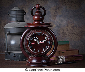 Group of objects on wood table. old clock, old rusty kerosene lamp ,old books , pencil, Still life