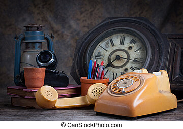Group of objects on wood table. old telephone, type writer, old camera, Still life