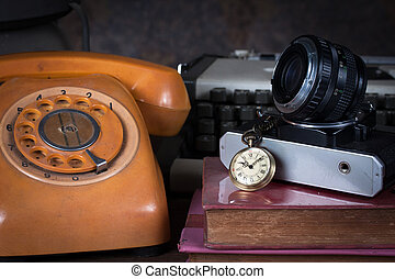 Group of objects on wood table. old watch, old telephone, old camera, type writer, Still life