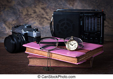 Group of objects on wood table. old watch, retro radio, camera, books, Still life