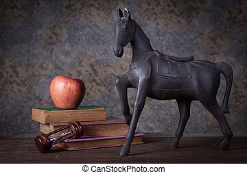 Group of objects on wood table. old wood horse, hourglass, old books , red apple, Still life