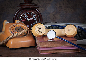 Group of objects on wood table. stethoscope, old telephone, old clock, type writer, Still life
