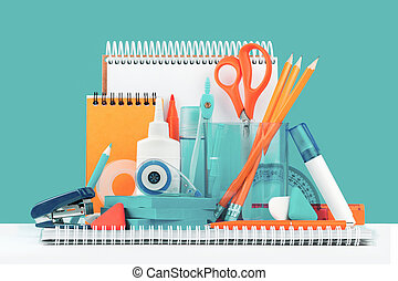 Group of office and school yellow orange and teal stationery on desk