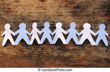 Group of paper chain people holding hands on the wood background