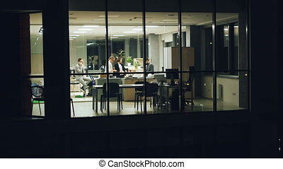 Group of people business team are working in office late at night talking on mobile phone, discussing job and looking at documents. View from outside from panoramic window.