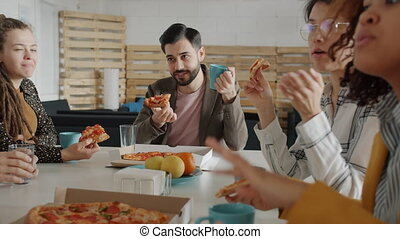 Group of young people colleagues are talking and laughing enjoying tasty pizza sitting at table in office. Corporate lifestyle and meal break concept.