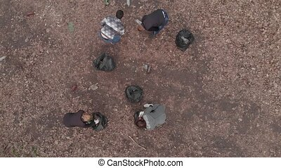 Young volunteers collecting garbage in park. Aerial view.