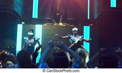Group of people dance in disco night club to the beat of music from DJ on stage