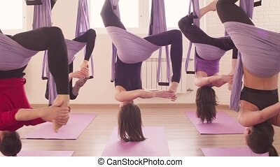 Group of people doing aerial yoga asanas in gym