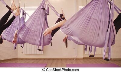 Group of people doing aerial yoga in gym