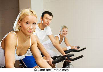 Group of people doing exercise on a bike in a gym