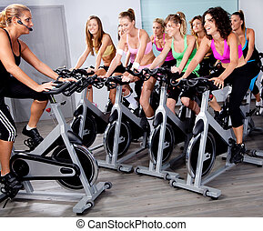 Group of people doing exercise on a bike - image of group of...