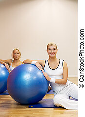 Group of people doing fitness exercise with a ball