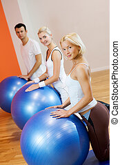 Group of people doing fitness exercise with a bal