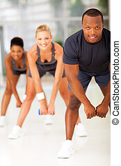 group of people doing fitness exercise with dumbbell
