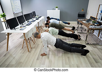 Group Of People Doing Pushups At Work