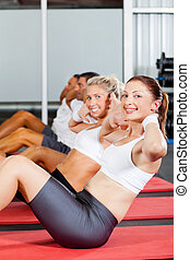 group of people doing situps in gym