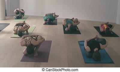 Group of people doing yoga asanas in studio