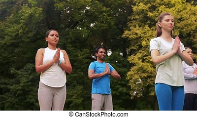 group of people doing yoga at summer park - fitness, sport ...
