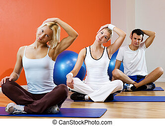 Group of people doing yoga exercise (focus on woman in the ...