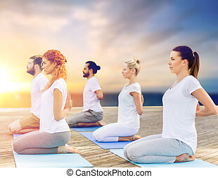 group of people doing yoga outdoors