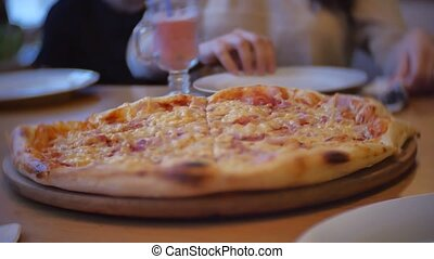 group of people eat pizza at a cafe. close-up children teens eating fast food in cafe slow motion video