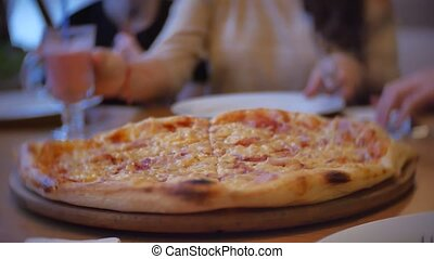 group of people eat pizza at a cafe. close-up children teens eating fast food in cafe slow motion video indoors
