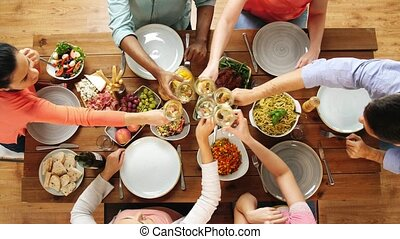 group of people eating and drinking wine at table - eating...
