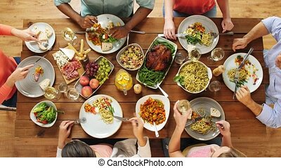 group of people eating at table with food - eating and...