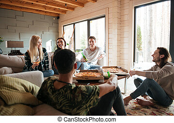 Group of people eating pizza and relaxing in living room