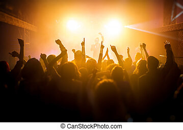 People silhouettes with raised hands enjoying a concert at nightclub