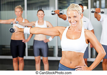 group of people exercise in gym