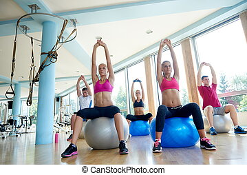 group of people exercise with balls on yoga class