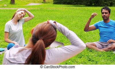 group of people exercising at summer park - fitness, sport ...
