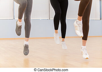 Group Of People Exercising In Dance Studio. feet of young people in fitness club