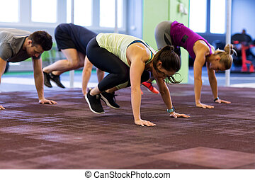 group of people exercising in gym - fitness, sport and...