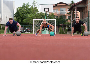 Group Of People Exercising Push-Ups On Medicine Ball