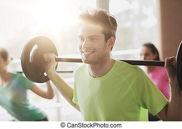 group of people exercising with barbell in gym
