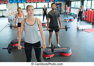 group of people exercising with barbell bars in gym