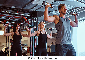 Group of people exercising with dumbbells in a fitness club or gym.