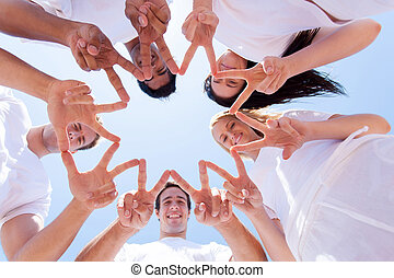 group of people hands forming a star shape outdoors