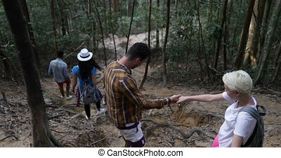 Group Of People Help Each Other To Walk Donwhill In Forest, Team Of Young Tourists On Hike Together