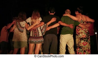 Group of people hugging at night, lit by campfire light (Package of 5 scenes, panning left, panning right, close up travelling right)