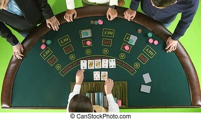 Group of people in casino betting, the dealer deals the...