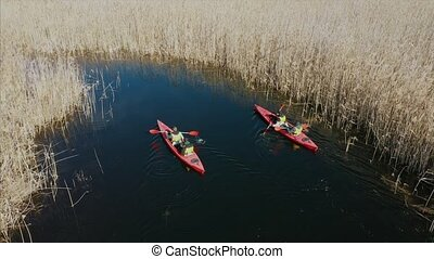Group of people in kayaks among reeds on the autumn river....