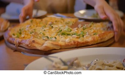 group of people indoors eat pizza at a cafe. close-up children teens eating fast food in cafe slow motion video