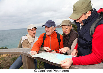 Group of people looking at map on a hiking day